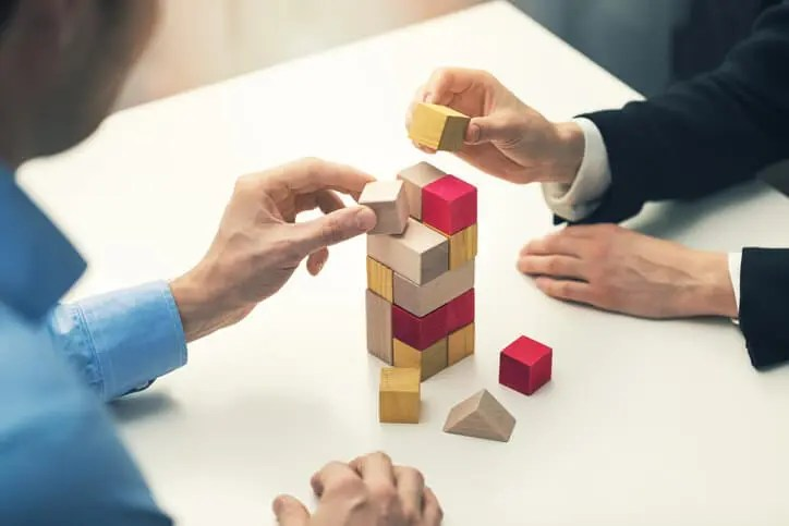 businesspeople building tower with blocks demonstrating social learning technology