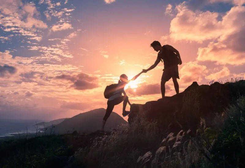 hikers helping each other up mountain representing knowledge sharing