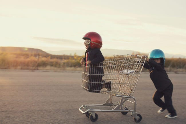 Young boy pushing second young boy in cart demonstrates push provided by best sales enablement tools