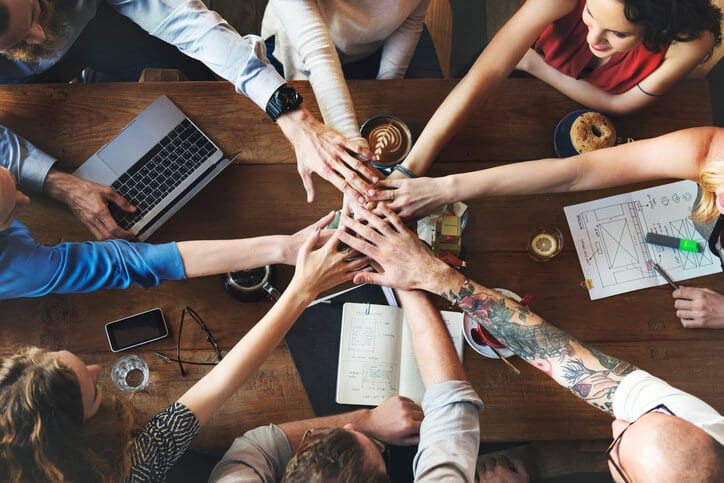 hands in the middle of a table cheering about building a customer success team