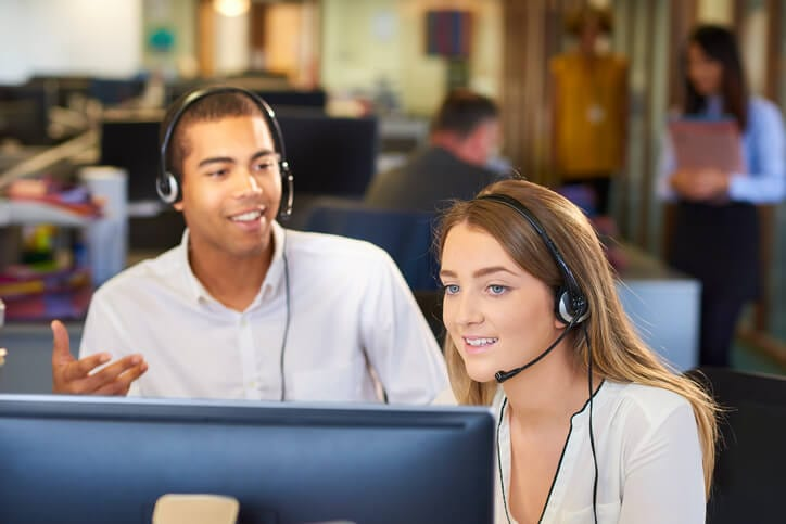 customer support reps with headsets demonstrate knowledge-centered support methodology