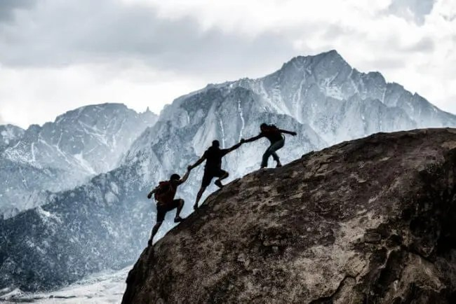 friends helping each other mountain climbing representing trustworthy content