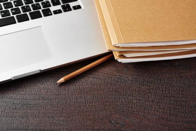 visualization of folder structure with manila folders next to laptop