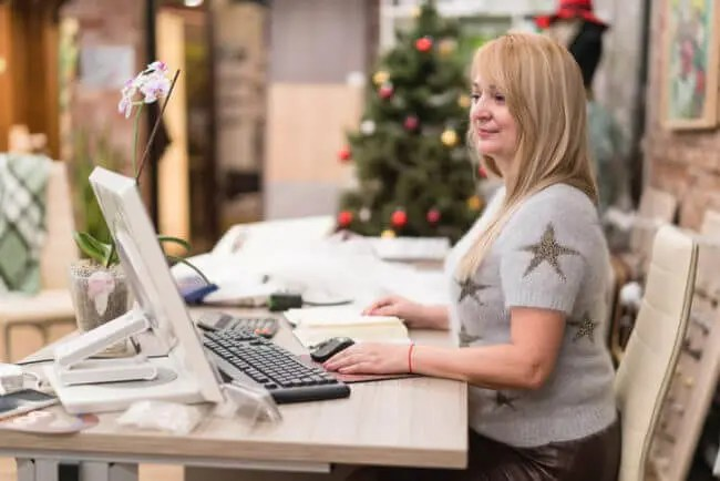 seasonal customer support rep at desk with Christmas tree in background