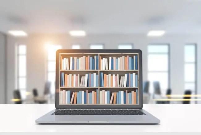 laptop with bookshelves shows knowledge base vs. knowledge sharing platform concept