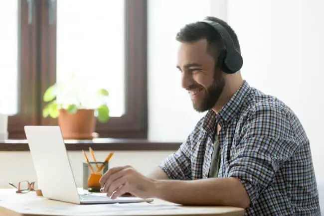 bearded man with headphones smiles while watching product training on laptop