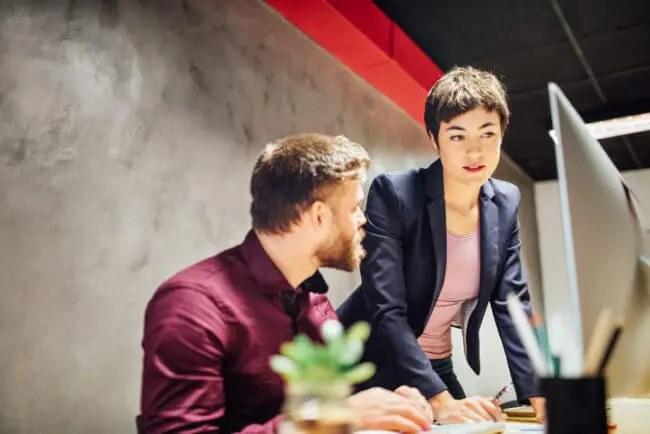 Sales and customer success team members meet at desk