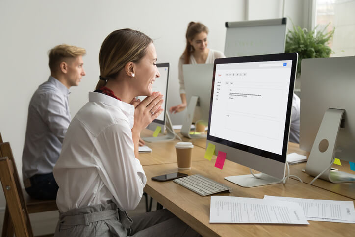 businesswoman smiling at computer is participating in channel incentive program