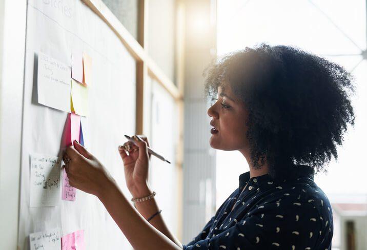 woman writes idea on sticky note demonstrating employee autonomy