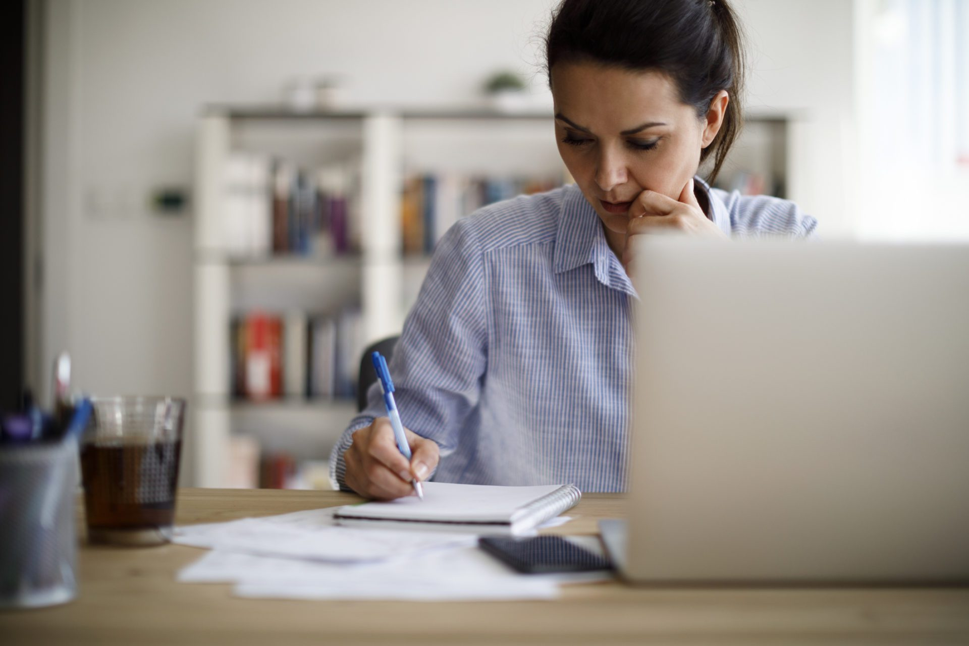woman at laptop taking notes to prevent knowledge silos