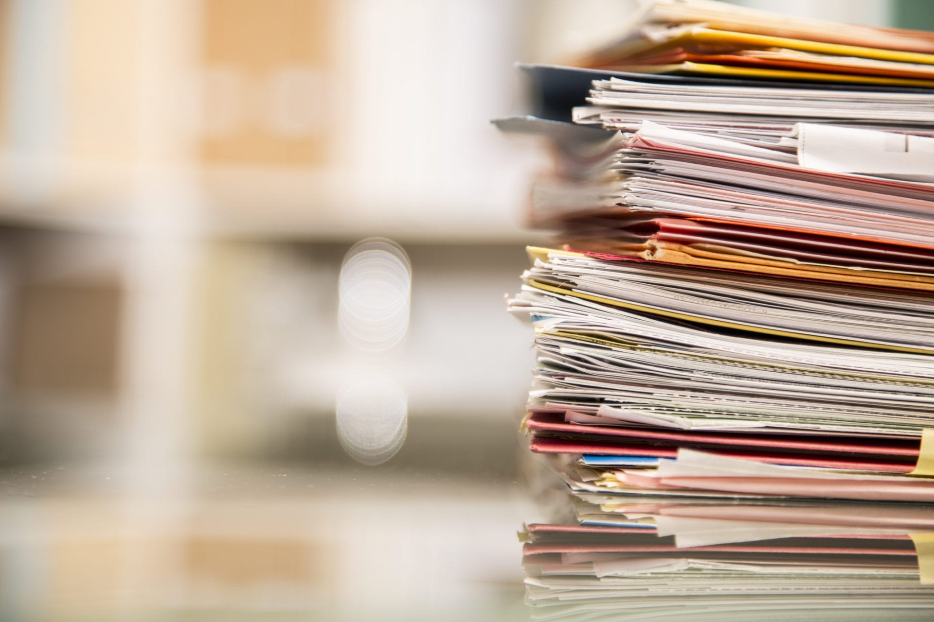 stack of folders on desk suggest it's time to upgrade knowledge management strategy