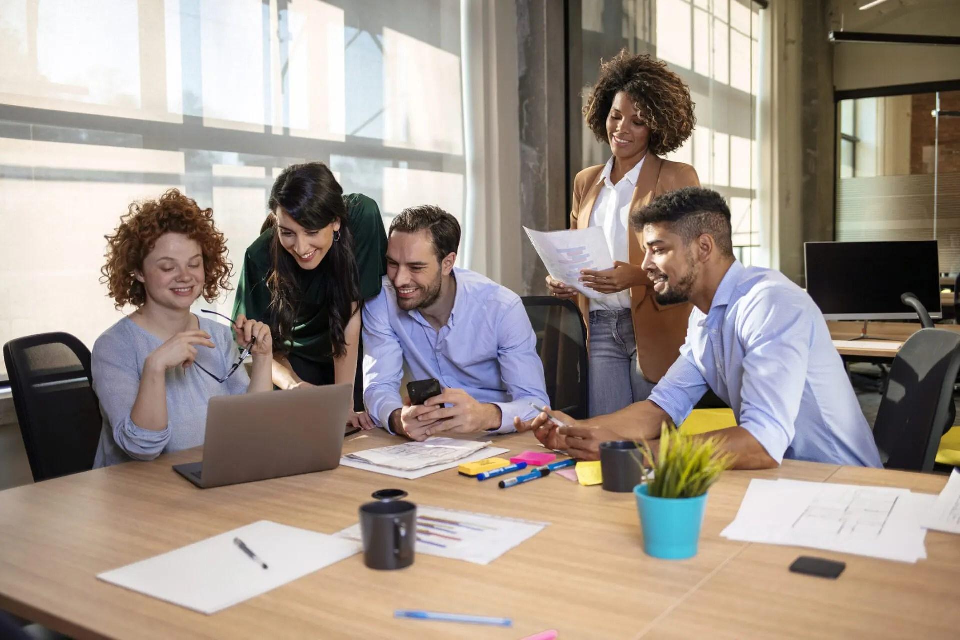 team gathers around laptop to plan knowledge management platform launch