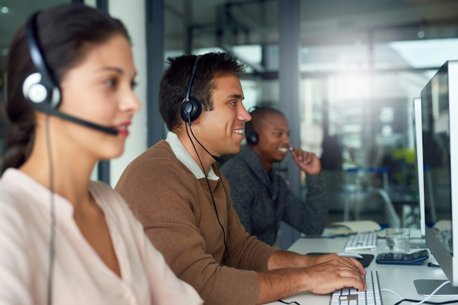 Call center employees at computers demonstrate employee engagement in customer service