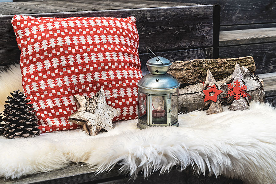 wooden veranda with lambskin, red and white Christmas pillows, lantern and firewood