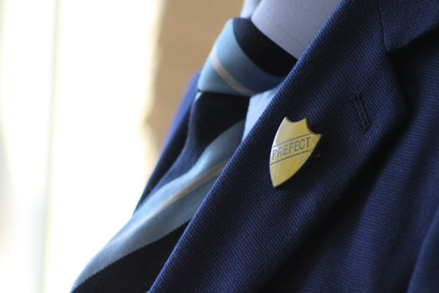 school uniform of a tie, blazer and shirt with a prefect badge