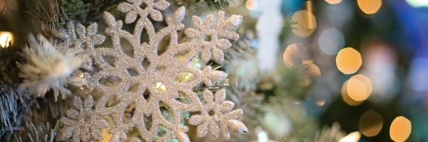 A white snowflake ornament hanging on a Christmas tree.