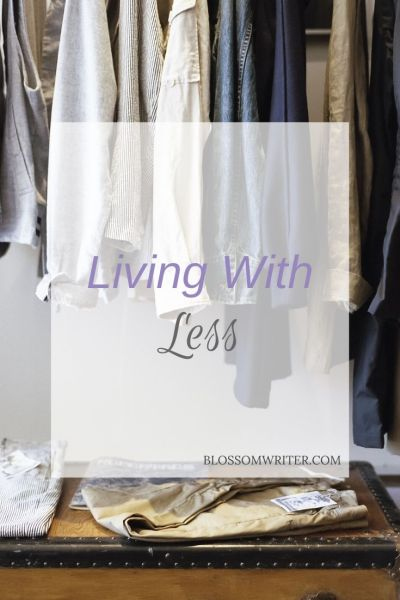 "A picture of clothes hanging in a closet. Text reads, ""Living With Less."""