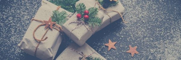 Christmas presents stacked together on a snow covered ground with wooden stars.