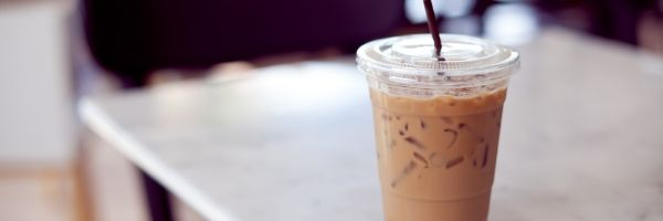 An iced coffee sitting on a white table.