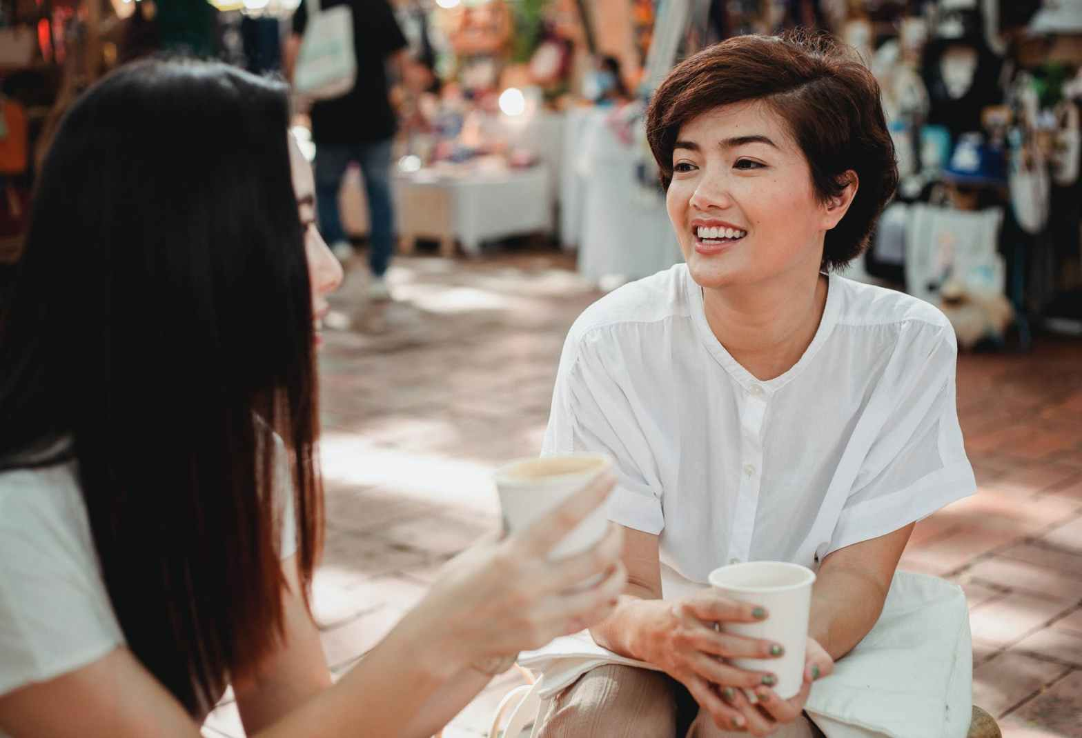 cheerful asian women enjoying coffee and chatting in outdoors cafe