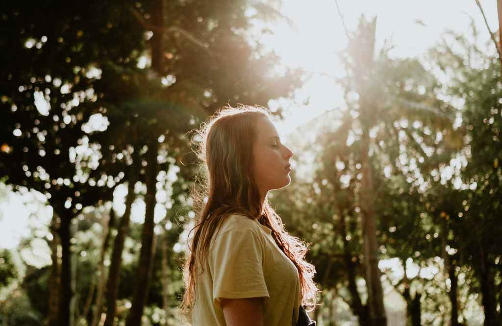 side view portrait photo of woman in yellow t shirt standing with her eyes closed with trees in the background