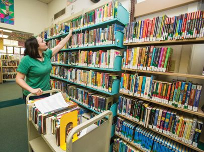 Library assistant shelving books