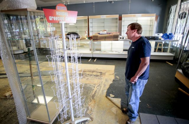 Ward Lundgren, owner of The Camera Co., surveys damage at his Odana Road store Wednesday. Losses including cameras, lenses, photo albums and the store's flooring are expected to surpass $100,000, via STEVE APPS, STATE JOURNAL