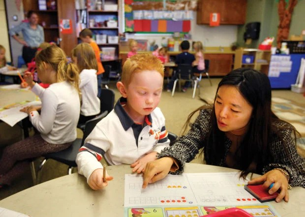 Kindergarten teacher Anastasia Lite Li works with student Sterling Mann