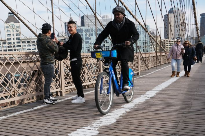 In this photo from February 12, 2020, bicyclists and pedestrians cross the Brooklyn Bridge in New York City.