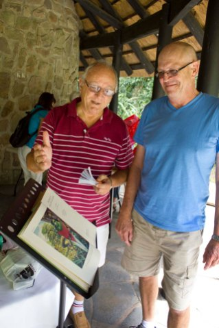 Norman Freeman informing Dave Bishop about the first edition book he has donated as a raffle.