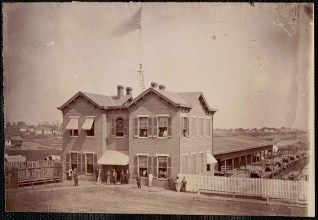 October 2020 D: Quartermaster Headquarters Alexandria Virginia: Brick building with awnings on windows, American flag flying above. Men outside and in windows. Storage shed behind building, white picket fence lower right to center, wooden fence lower left to center.