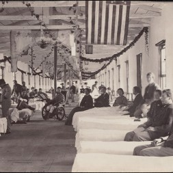 October 2020 F: Ward in Armory Square Hospital, Washington, DC: 1864. Nurses and orderlies attending group of wounded men in hospital. Row of U.S. flags hanging from ceiling.