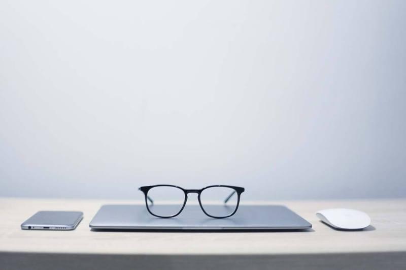 MacBook Airと手帳と眼鏡を広げたデスク