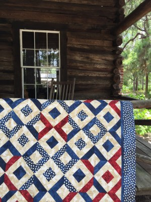 Sparklers on Liberty Square Quilt on log cabin porch