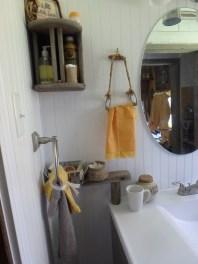 old napkin holder, weathered for shelf, above pieces of old weathered ladder for another shelf and a snaffle bit as towel/hankie holder
