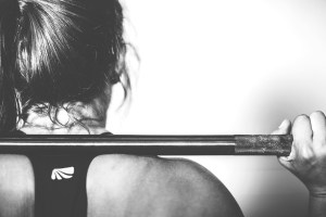 A woman holding a crossfit bar.