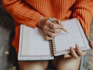 A woman making notes in a calendar.