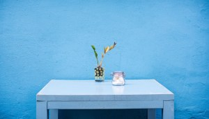 A blue desk in front of a blue wall.