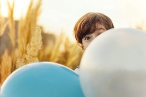 boy hiding behind balloons