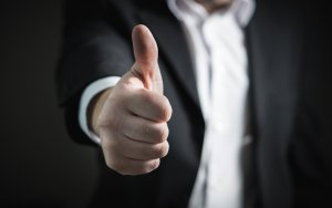 A man in a suit giving a thumbs up