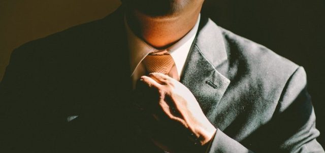 A man in a suit fixing his tie
