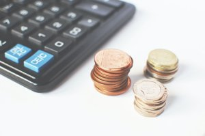 coins and a calculator on a white table