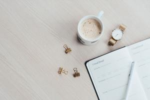 mug, watch and a planner on a desk