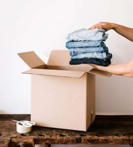 Person packing clothes in a cardboard box.