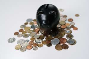A pile of coins and a piggy bank