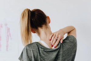 a young woman pointing to her neck which is hurting