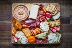 a plate with snacks, cheese, meat, souce, bread.