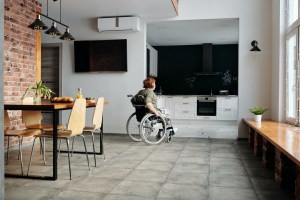 make your Newark home wheelchair accessible by lowering the cabinets in the kitchen, a woman in a wheelchair approaching the kitchen