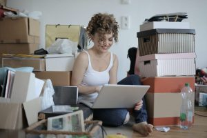 woman sitting on the floor, using laptop, smiling, boxes and clutter around her