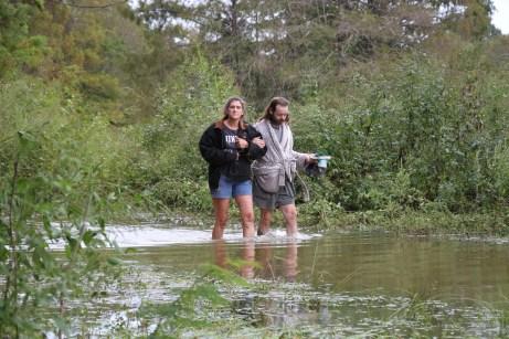 Two residents of Sam Houston Lake Estates walk through floodwaters on Tuesday.